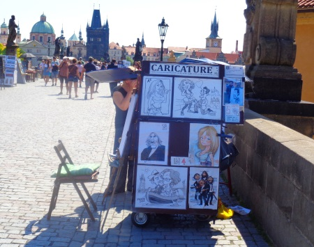 Person drawing people on Charles Bridge
